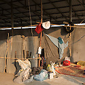 Cambodia - Kampong Speu Province - Labour tools hanging next to lady bags in the camps where sugar plantation workers live nearby the Phnom Penh Sugar Company factory, in the Amliang commune. Most of them come from villages far away in the province to work in the sugar plantation during the dry season. Without a proper home they sleep in makeshift tents and beds in a concrete structure provided by the company. Some of them are able to save as little as 5 USD per month.
