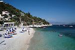 Greece, Corfu, Kaminaki Beach: View along busy beach