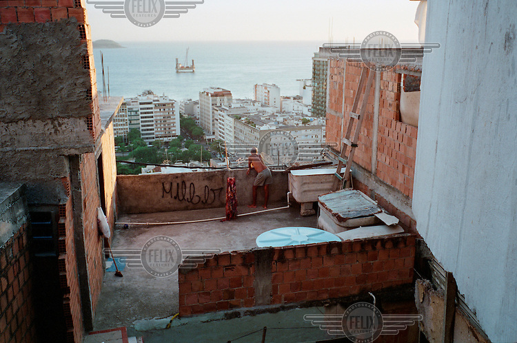 A man looks out onto the wealthy district of Ipanema from his home in the Cantagalo favela. People often joke that the poorest have the best view of the bay.