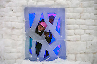 Moscow, Russia, 14/01/2012..Two women peer out from inside an ice prison cell in Moroz City, or Frost City, an ice town constructed in Moscow's Sokolniki Park by a team of architects and ice sculptors. As well as ice sculptures the temporary town features a disco, hotel, fitness centre, post office and prison.