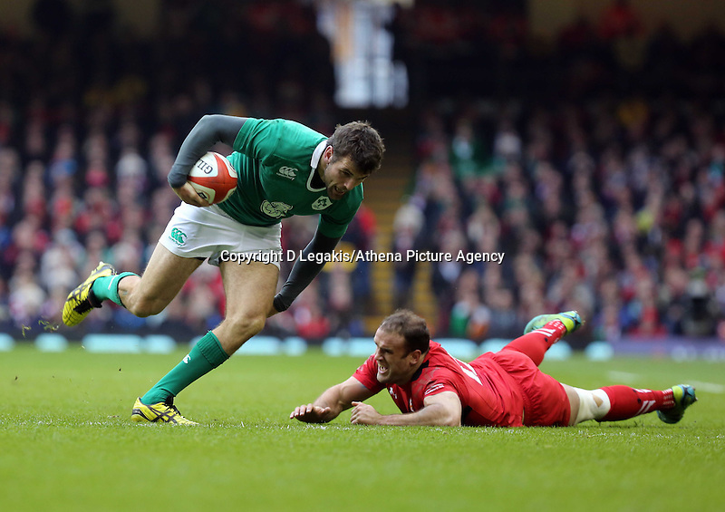 Pictured: Jared Payne of Ireland (L) avoids Jamie Roberts (R) of Wales Saturday 14 March 2015<br /> Re: RBS Six Nations, Wales v Ireland at the Millennium Stadium, Cardiff, south Wales, UK.