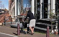 Nederland Amsterdam- 2020.  Hoogbejaarde vrouw met hoedje loopt achter een rollator.   Foto ANP / Hollandse Hoogte / Berlinda van Dam