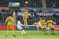 Dan Burn of Wigan Athletic (C) heads the ball away from Wilfried Bony of Swansea City (2nd L) during the Sky Bet Championship match between Swansea City and Wigan Athletic at the Liberty Stadium, Swansea, Wales, UK. Saturday 29 December 2018