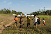 Mato Grosso State, Brazil. Aldeia Metuktire (Kayapo). Funai plane leaving  the airstrip, boys enjoying the wake from the engines.