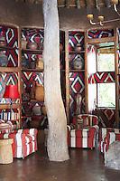 Seating with red and white patterned upholstery in a sitting area at the Singita Pamushana Lodge, Malilongwe Trust, Zimbabwe