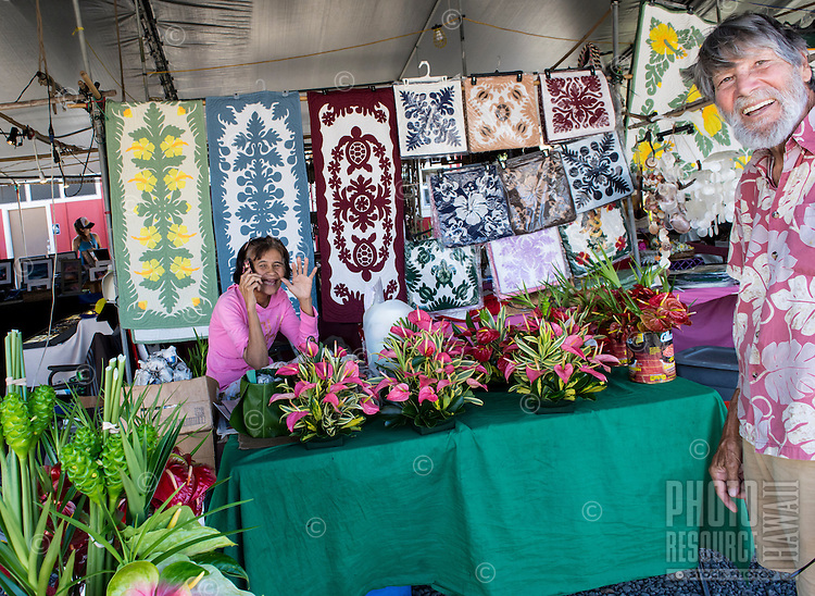 An aunty holding her cell phone waves and a local senior resident smiles at the viewer at the Hilo Farmers Market on the Big Island of Hawai'i. (Note: The man is model released, the woman is not.)