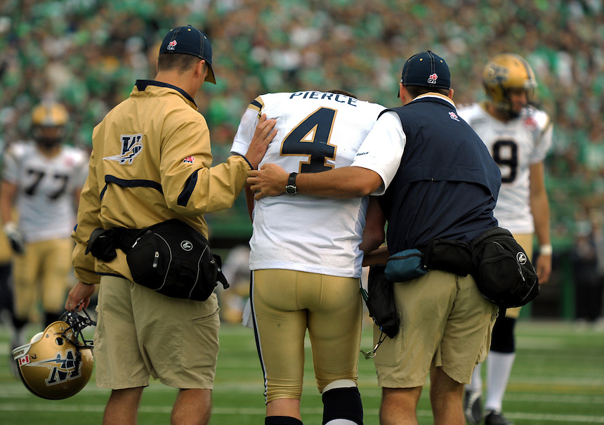 Winnipeg Blue Bombers' quarterback Buck Pierce is helped off the field after sustaining an injury late in the game during the Labour Day Classic in Regina Sunday, September 5, 2010. THE CANADIAN PRESS/Mark Taylor.