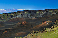 Cinder cones are visible in the crater of HALEAKALA NATIONAL PARK on Maui in Hawai with the Big Island of Hawaii in the backgroundi