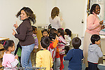 New York City preschool ages 2-3 music dance activity female teachers and group of children singing song and moving to music horizontal