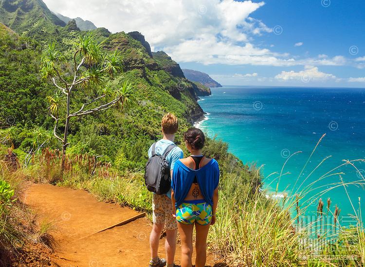 Two hikers take in the view of Hanakapi'ai Beach and Na Pali (or Napali) coastline from the Kalalau Trail, northern Kaua'i.