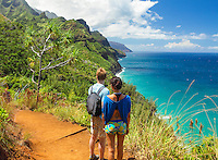 Two hikers take in the view of Hanakapi'ai Beach and Na Pali (or Napali) coastline from the Kalalau Trail, northern Kaua'i.