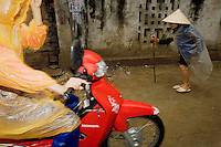 Vietnam. Ha Tay province. Lai Xa. An old woman, wearing the traditional vietnamese hat and her body covered with plastic sheetings as a rain protection, walks on the road while a woman rides her red Honda motorcycle. No floods on the main road after a heavy rain. Through the construction of a main drainage and the building of sewerage as a combined system, collecting both rainwater and domestic waste water, the implementation of a flexible decentralized community sanitation project in a context of low infrastructure investment and in a peri-urban case study, such as Lai Xa, is a major sucesss. It offers importants benefits as an alternative to centralized systems, namely in terms of health improvements and by the possibility of dealing with wastewater locally, through households and decentralized municipal structures. Lai Xa is a typical hamlet (village) of the Red River delta region and is part of the Kim Chung commune located 15 km west of Hanoi. This peri-urban location is under increasing pressure from the forces of urbanization. 05.04.09  © 2009 Didier Ruef