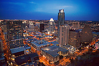 Aerial View from a helicopter of the Downtown Austin, Texas Skyline Cityscape at dusk as the Skyscrapers stand illuminated contrasting the nighttime sky