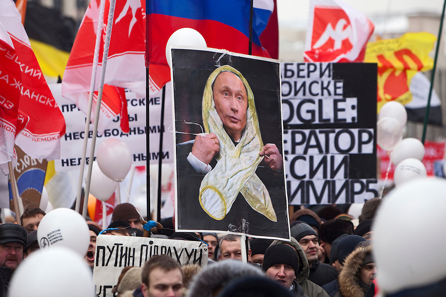 """Moscow, Russia, 24/12/2011..A placard with an image of Vladimir Putin wrapped in a condom, a response to Putin's description of opposition protestors' white ribbons """"looking like condoms"""". An estimated crowd of up to 100,000 protested against election fraud and Prime Minister Vladimir Putin in the largest anti-government demonstration in Russia since the collapse of the Soviet Union."""