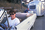 Wife is sitting in the driver's side of the 1965 Chevrolet Malibu convertible while her husband is hitching a vintage 1965 Caravel Airstream to the car.