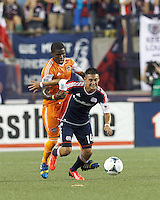 New England Revolution midfielder Diego Fagundez (14) controls the ball as Houston Dynamo defender Kofi Sarkodie (8) pressures. In a Major League Soccer (MLS) match, Houston Dynamo (orange) defeated the New England Revolution (blue), 2-1, at Gillette Stadium on July 13, 2013.