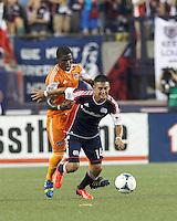New England Revolution midfielder Diego Fagundez (14) controls the ball as Houston Dynamo defender Kofi Sarkodie (8) pressures. In a Major League Soccer (MLS) match, Houston Dynamo (orange) defeated the New England Revolution (blue), 2-1, at Gillette Stadium on July 13, 2013.