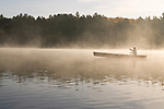 A woman paddles a red canoe on Galerairy lake in the early morning mist in Ontario's Algonquin Provincial Park in Canada.
