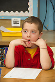 MR / Schenectady, New York. Yates Arts-in-Education Magnet School (urban public school). First grade classroom. Student (boy, 6) makes a funny face as he sits at his desk and listens in class. MR: Ken11. ID: AM-g1w. © Ellen B. Senisi.