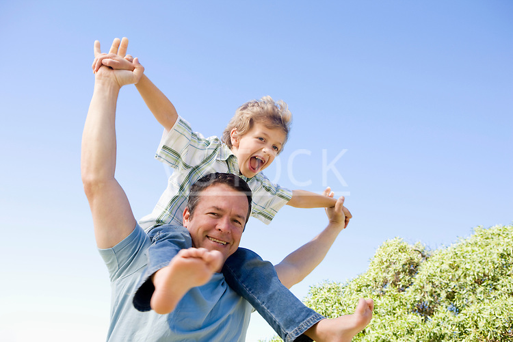 Father carrying son (8-9) on shoulders