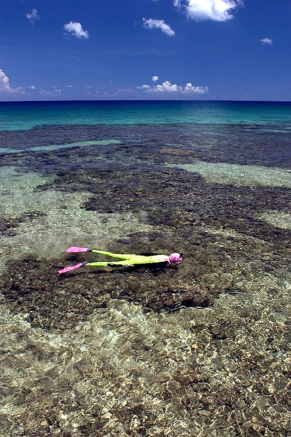 Woman (MR) snorkeling over a shallow reef in Cayman Brac, Cayman Island