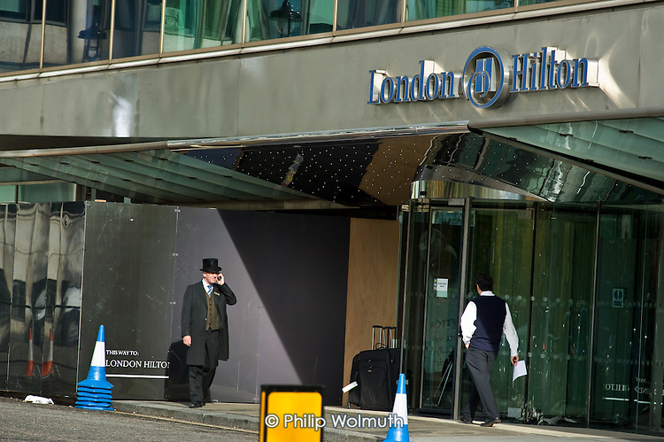 A doorman in a top hap outside the London Hilton hotel in Park Lane, Mayfair.