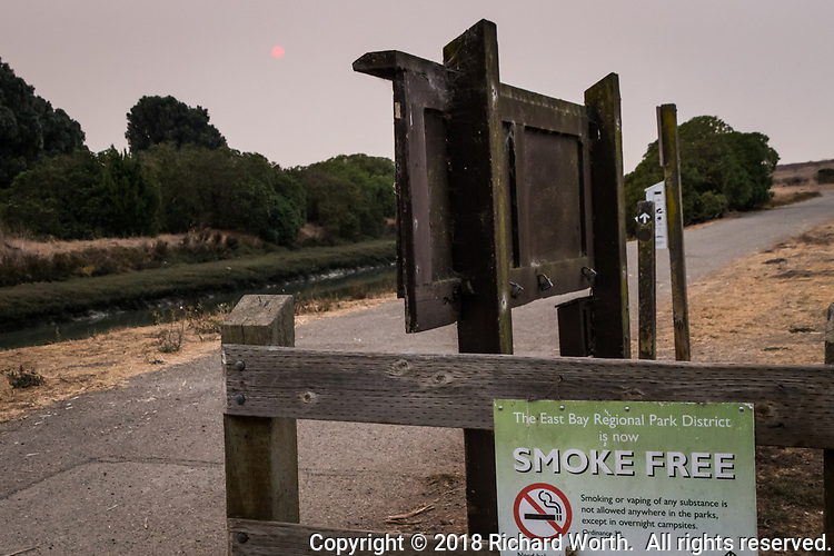 A sign declares a park district 'Smoke Free' while smoke from a wild fire 150 miles away fills the sky painting the sun red.