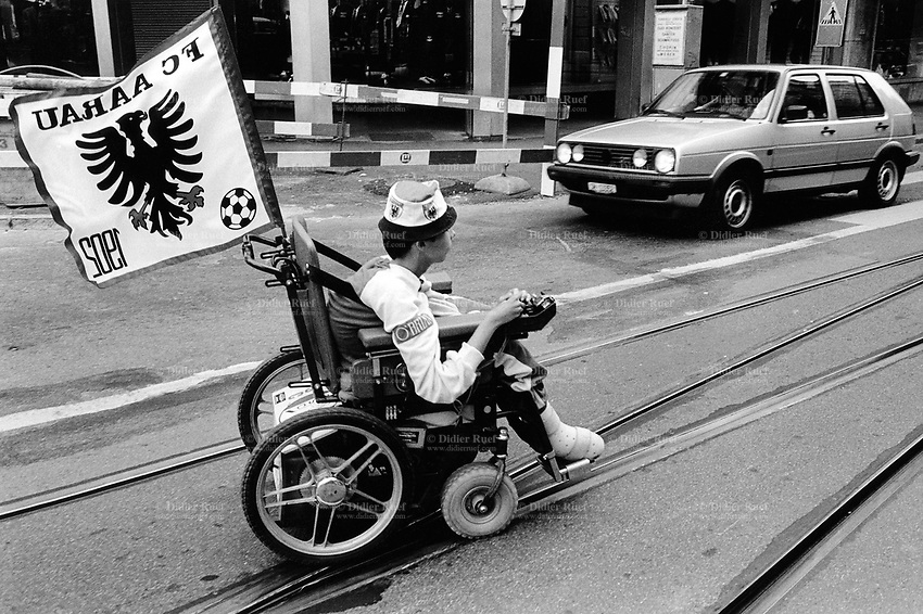 Switzerland. Zürich. A young soccer fan from the FC Aarau football club rides the road on his wheelchair with the assistance of an electrical engine. He crosses a VW Golf car on the street. © 1990 Didier Ruef