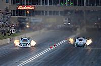Jul, 20, 2012; Morrison, CO, USA: NHRA funny car driver John Force (left) races alongside team mate Mike Neff during qualifying for the Mile High Nationals at Bandimere Speedway. Mandatory Credit: Mark J. Rebilas-US PRESSWIRE