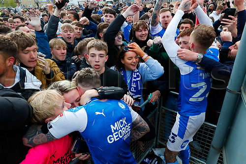 1st May 2021; Weston Homes Stadium, Peterborough, Cambridgeshire, England; English Football League One Football, Peterborough United versus Lincoln City; Sammie Szmodics of Peterborough United hugs his wife and daughter as fans celebrate with players outside The Weston Homes Stadium after Peterborough United win promotion to the EFL Championship