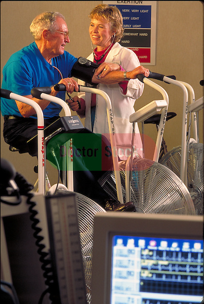 smiling nurse taking blood pressure of elder on exercise machine