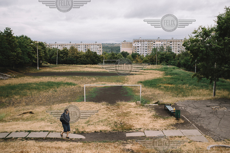 A woman walks past a football pitch in the Ciocana district.