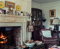 A log fire burns brightly in the large living room fireplace  and next to it is a comfortable leather armchair