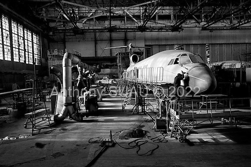 """Samara, Russia  .October 1997.""""Aviacor""""-Russian joint stock company produces and repairs TU-154M passenger planes. A worker repairs a plane in one of the only factory hangers which still operates. This Russian industry is in serious trouble today.."""