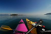 View from cockpit of purple kayak tied up with yellow kayak, Sea Kayaking the San Juan Islands, WA.