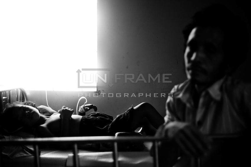 Child with dengue fever  and her father - typical patients' room scene.  Unfortunatelly health care workers in Cambodia are not always sufficiently qualified in the issues of pediatric health, families often lack proper health care knowledge. National Pediatric Hospital of Phnom Penh. Cambodia
