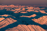 The sun sets over the Alaska range, creating an intriguing pattern of layers and shadows.  Photographed from a bush plane flight over the range.