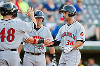 Andrew Lambo (38) of the Indianapolis Indians is greeted at home plate by his teammates after hitting a 3-run home run against the Charlotte Knights at Knights Stadium on July 22, 2012 in Fort Mill, South Carolina.  The Indians defeated the Knights 17-1.  (Brian Westerholt/Four Seam Images)