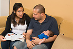 Young couple looking at advice book, father holding newborn baby boy, in living room at home