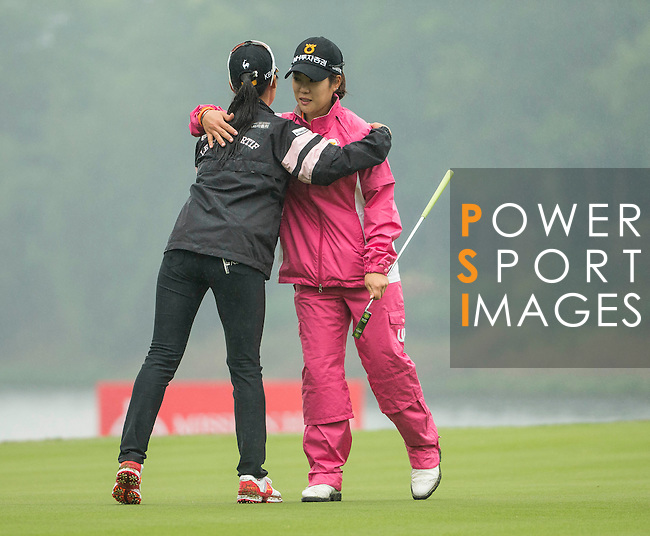 Seung Hyun Lee of South Korea (right) hugs Ji Hyun Oh of South Korea (left) at the end of their game at the 18th hole during Round 4 of the World Ladies Championship 2016 on 13 March 2016 at Mission Hills Olazabal Golf Course in Dongguan, China. Photo by Victor Fraile / Power Sport Images