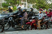Yogyakarta, Java, Indonesia.  Evening Traffic,  Jl. Laksda Adisucipto Street.  Note woman wearing breathing mask.