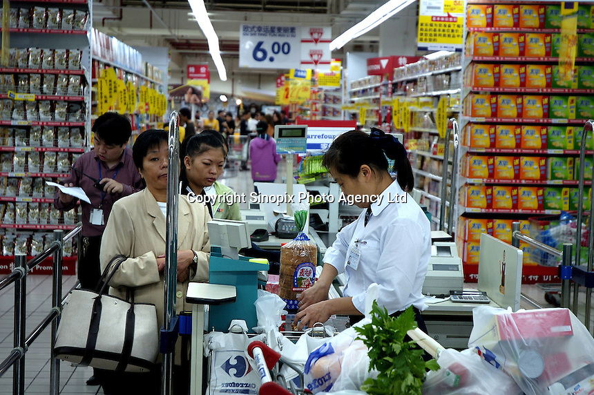 Customers at a checkout counter of successful French supermarket chain Carrefour's main store in Shanghai.