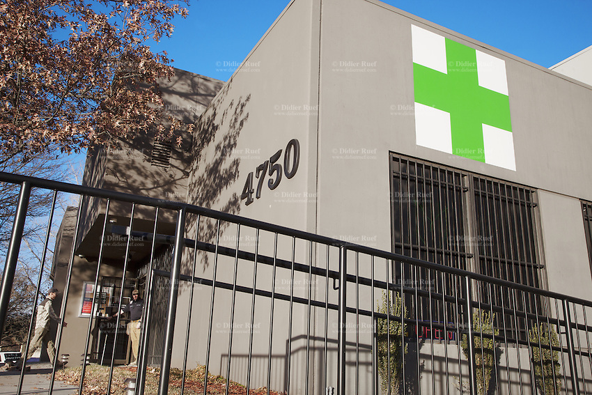 USA. Colorado state. Denver. The warehouse of Medicine Man at 4750 Nome St. in an industrial section of Denver's Montbello neighborhood. Sixty-five video cameras are trained on the property and security guards patrol the alley and control the entrance. The Green Cross flag is the symbol of a Medical Marijuana Dispensary. Medicine Man began nearly six years ago as a small medical marijuana operation and has since grown to be the largest single marijuana dispensary, both recreational and medical, in the state of Colorado and has aspirations of becoming a national brand if pot legalization continues its march. Cannabis, commonly known as marijuana, is a preparation of the Cannabis plant intended for use as a psychoactive drug and as medicine. Pharmacologically, the principal psychoactive constituent of cannabis is tetrahydrocannabinol (THC); it is one of 483 known compounds in the plant, including at least 84 other cannabinoids, such as cannabidiol (CBD), cannabinol (CBN), tetrahydrocannabivarin (THCV), and cannabigerol (CBG). 19.12.2014 © 2014 Didier Ruef