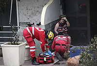 Pictured: Paramedics see to an elderly woman in the Mati area, Kokkino Limanaki near Rafina, Greece. Tuesday 24 July 2018<br /> Re: Deaths caused by wild forest fires throughout Greece.