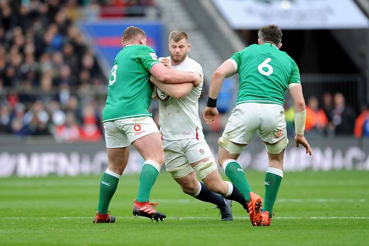 George Kruis of England is tackled by Tadhg Furlong of Ireland as Peter O'Mahony of Ireland looks on during the Guinness Six Nations match between England and Ireland at Twickenham Stadium on Sunday 23rd February 2020 (Photo by Rob Munro/Stewart Communications)