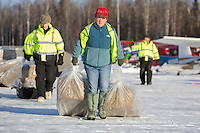 Volunteer Iditarod Air Force pilots, Diana Moroney and Greg Niesen move straw to waitng Iditarod Air Force planes at the Willow, Alaska airport during the Food Flyout on Saturday, February 20, 2016.  Iditarod 2016