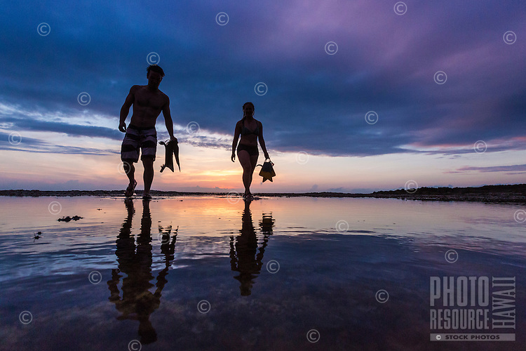 A couple holding snorkeling gear walk across tidal rocks at sunset at Shark's Cove, North Shore of O'ahu.