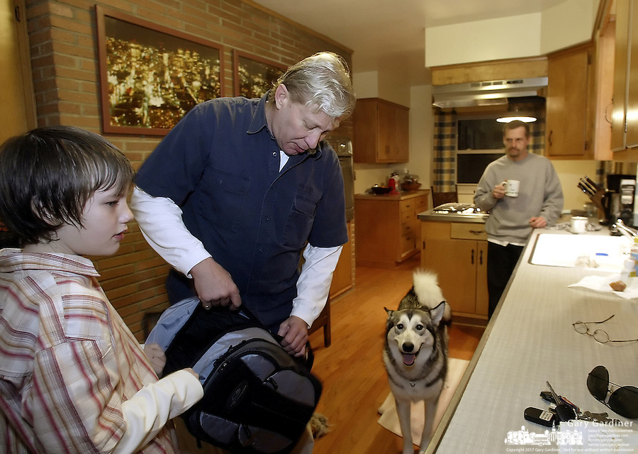 10-year-old Michael O'Reilly-Birtcher, left, gets help with his back from his adoptive father Thom O'Reilly, center, as his othger adoptive father Harold Birtcher and their dog Alaska look on in their home Thursday, Feb. 16, 2006, in Upper Arlington, Ohio. Because same-sex partners are barred from joint adoption in Ohio, O?Reilly and Birtcher, who have been together for 25 years, went to Oregon three years ago to jointly adopt Michael. A bill introduced in the Ohio Legislature this month would bar all gays and lesbians from adoptions and foster care.<br />