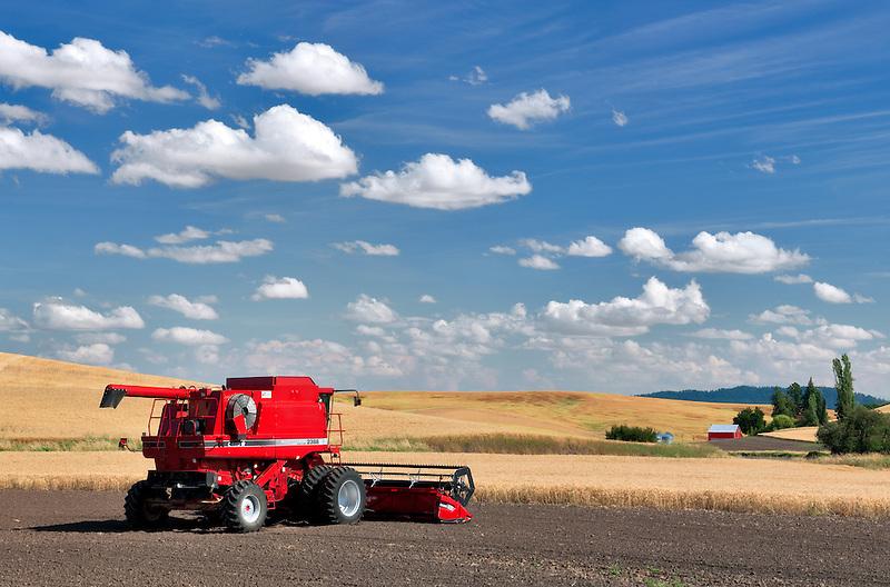 Combine harvester in newlt plowed field with wheat fields. The Palouse, Washington