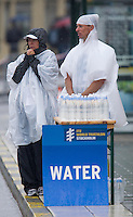 26 AUG 2012 - STOCKHOLM, SWE - Race crew wait  in the rain by their water station during the 2012 ITU Mixed Relay Triathlon World Championships in Gamla Stan, Stockholm, Sweden .(PHOTO (C) 2012 NIGEL FARROW)